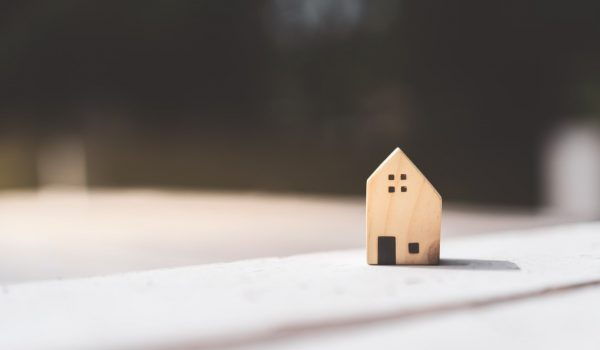 Small,Home,Model,On,Wooden,Table,With,Nature,Green,Bokeh